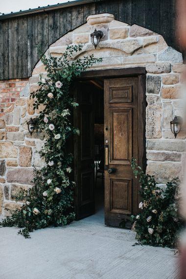 Wedding Floral Arrangement Lining the Doorway to the Wedding Venue