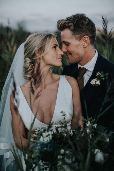 Bride in Jesus Peiro Wedding Dress and Groom in Dark Suit Embracing in the Fields