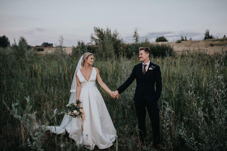 Bride in Jesus Peiro Wedding Dress and Groom in Dark SuitHolding Hands in the Fields