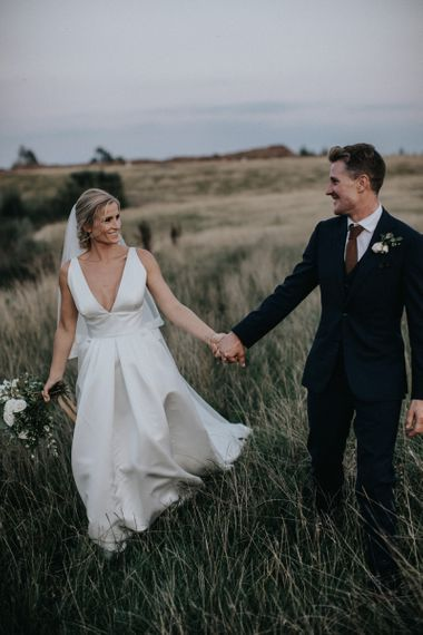 Smiling Bride in Jesus Peiro Wedding Dress and Groom in Dark SuitHolding Hands in the Fields