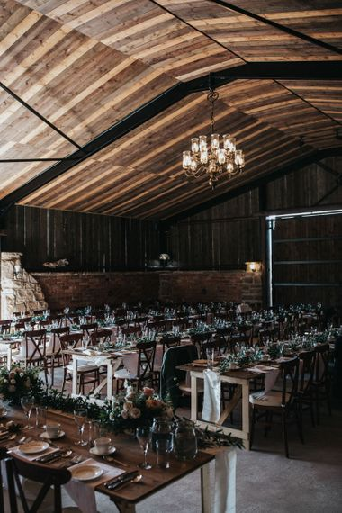 Rustic Luxe Barn Wedding Venue with Chandelier , Wooden Tables and Greenery Table Runners