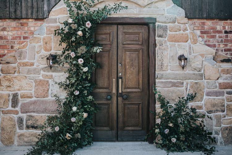 Wooden Door with Greenery and White Flower Arrangement by Number Twenty Seven