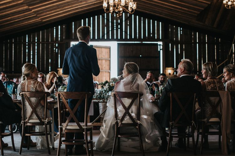 Grooms Speech in Dark Navy Suit  at a Rustic Luxe Barn Wedding Venue