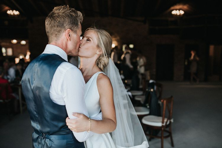 Bride in Jesus Peiro Wedding Dress  and Groom in Waistcoat Kissing During their First Dance