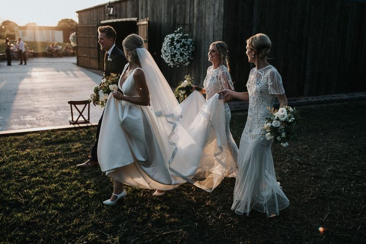 Bridesmaids in Embellished White Dresses Holding the Brides Jesus Peiro  Train Up