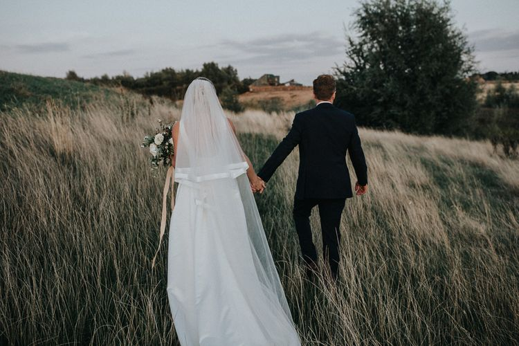 Bride in Jesus Peiro Wedding Dress and Satin Trimmed Veil and Groom in Navy Suit Walking Through the Fields
