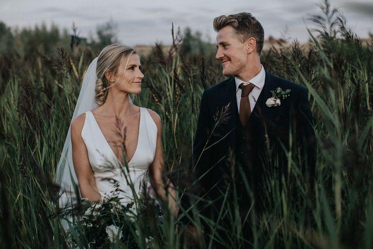 Bride in Jesus Peiro Wedding Dress and Groom in Navy Suit Standing in the Fields
