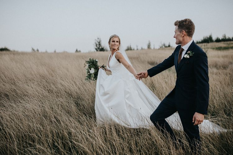 Bride in Jesus Peiro Wedding Dress and Groom in Navy Suit Holding Hands Walking Through the Fields
