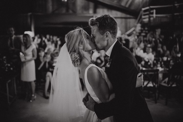 Black and White Portrait of Bride in Jesus Peiro Wedding Dress  and Groom Kissing During their First Dance