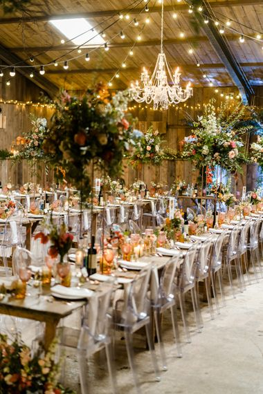 Chandelier, Large Floral Arrangements & Ghost Chairs For Rustic Luxe Wedding // The Barn At South Milton Wedding With Outdoor Humanist Ceremony And Floral Arch By Flowers By Passion Images From John Barwood Photography