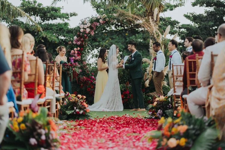 Bride and groom exchange vows in front of floral moon gate