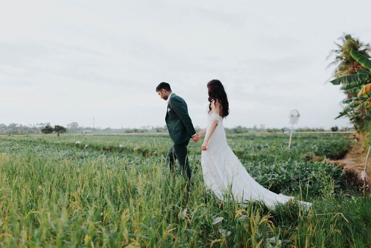 Bride and groom make their way over fields