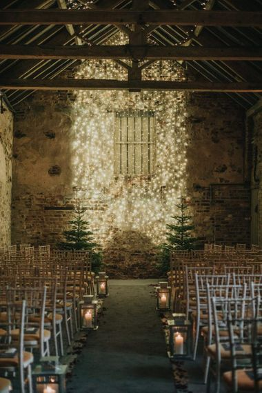 Fairy light curtain for New Years eve ceremony in a barn with Christmas trees and lantern aisle decor