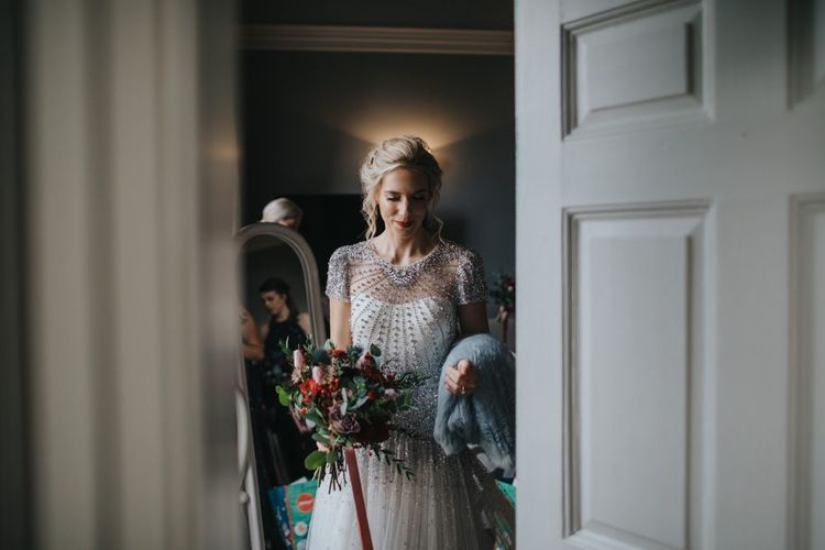 Bride wearing a beautiful embellished wedding dress with festive floral bouquet and a classic red lip