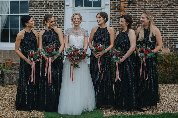 Bride wearing a beautiful embellished wedding dress and a classic red lip with her bridesmaids in black dresses and festive bouquets