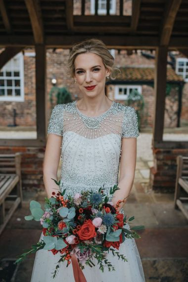 Close up detail of brides embellished wedding dress teamed with a red lip and a festive floral bouquet