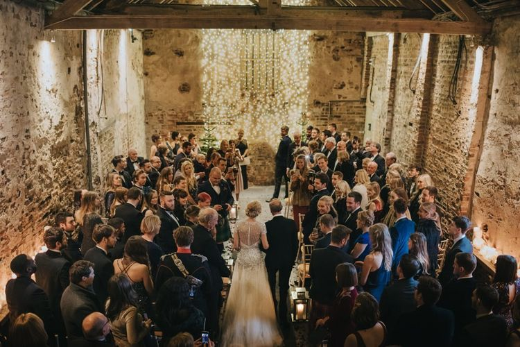Winter ceremony with candle lantern aisle and a fairy light curtain with Christmas trees