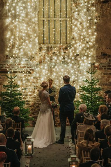 Bride and groom tie the knot at winter ceremony wearing a embellished wedding dress and navy velvet suit with fairy light curtain and Christmas trees