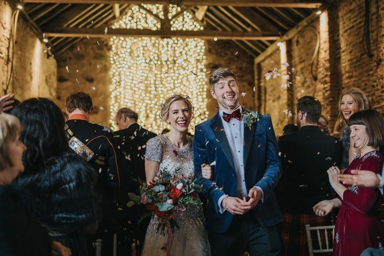 Confetti shot at winter wedding in a barn with fairy light curtain and embellished wedding dress