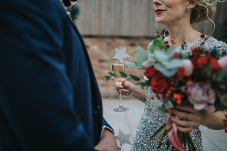 Bride and groom at winter styled wedding with red floral bouquet and a navy velvet suit