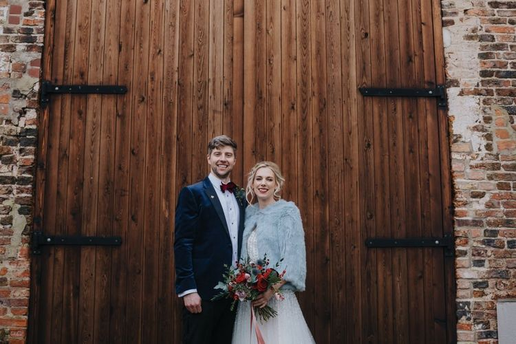 Bride wearing embellished wedding dress and jacket at winter wedding ceremony with red floral bouquet
