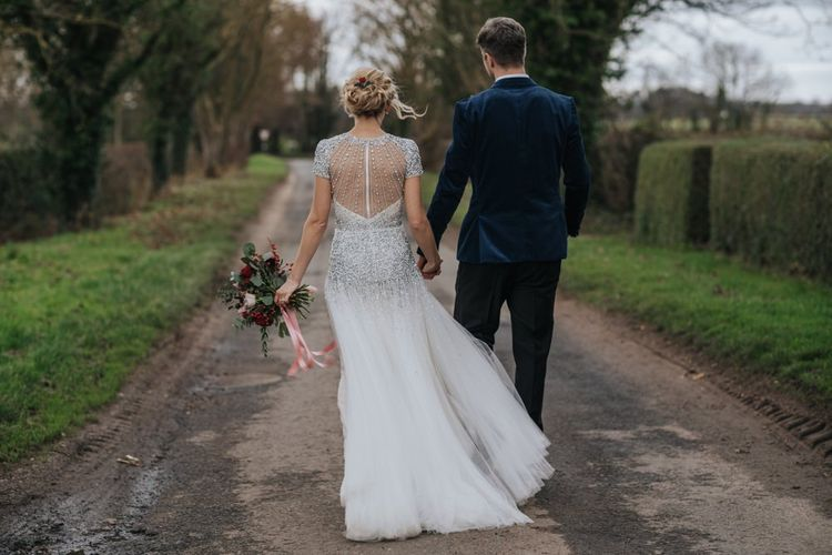 Back of brides embellished wedding dress with groom wearing a navy velvet suit at winter wedding