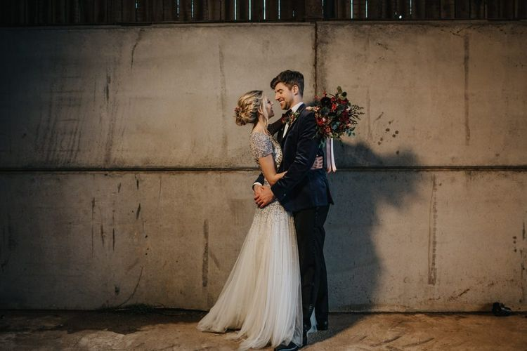 Bride and groom embrace at winter wedding wearing an embellished wedding dress and navy velvet suit