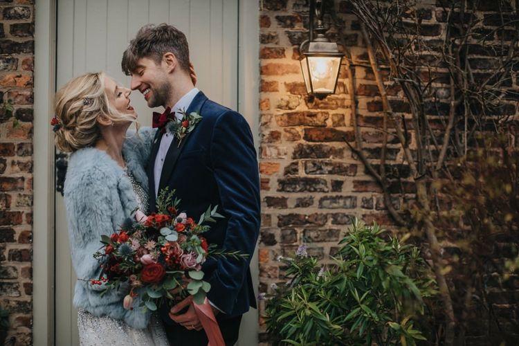 Bride and groom embrace at winter wedding wearing an embellished wedding dress and blue bridal jacket