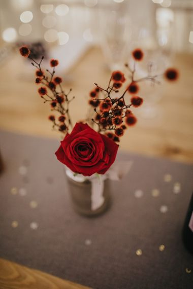 Red rose floral table decor at winter reception with fairy lights