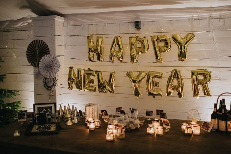 'Happy New Year' balloons for marquee winter reception with fairy lights and candles
