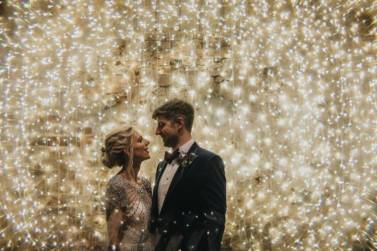 Bride and groom embrace with fairy light curtain at New Years eve wedding