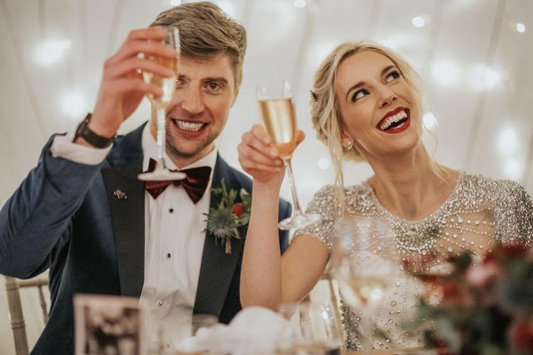 Bride wearing an embellished wedding dress and classic red lip for winter wedding reception