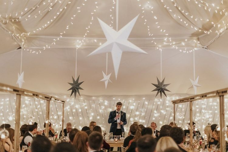 Grooms speech at marquee winter reception styling with star decor and fairy lights for New Years eve celebration