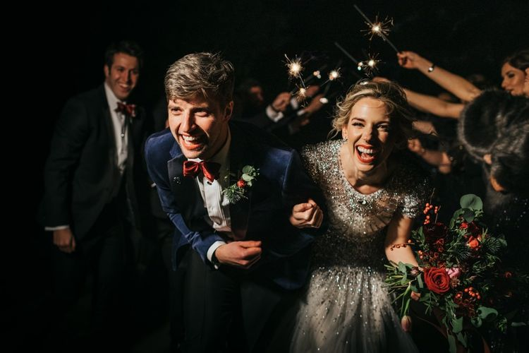 Bride and groom confetti exit wearing embellished wedding dress and red rose floral bouquet