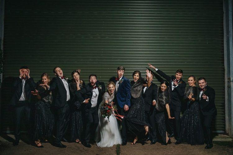 Bride and groom with  groomsmen in black tie and black bridesmaid dresses