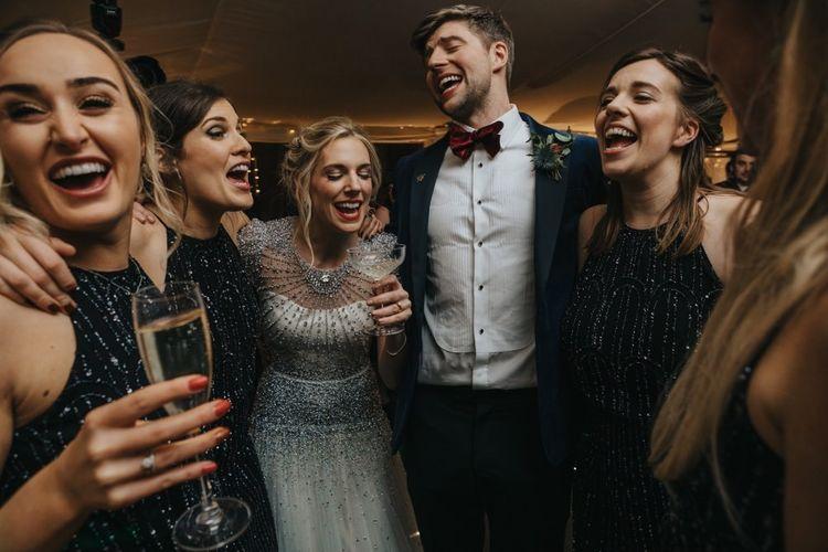 Bride wearing embellished wedding dress and bridesmaids in black dress with black tie winter wedding