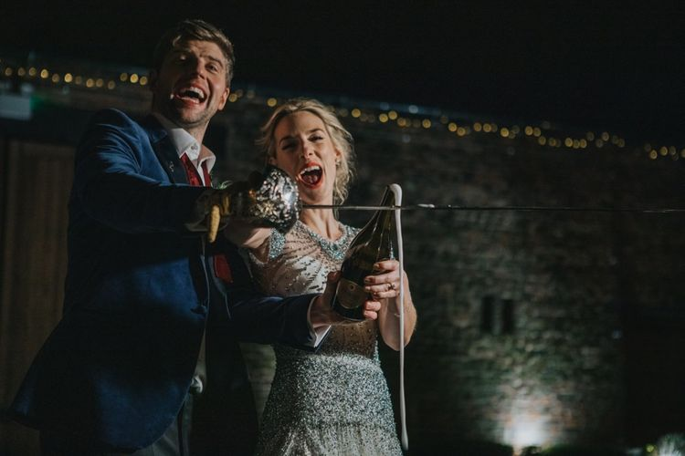 Bride and groom using a sword to open a bottle of champagne at winter reception