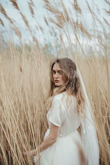 Bride in Susanna Greening Designs wedding dress and veil with long wavy hair