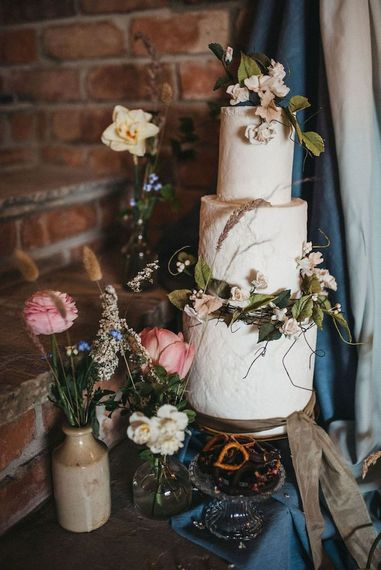 Buttercream wedding cake decorated with seasonal Spring wedding flowers
