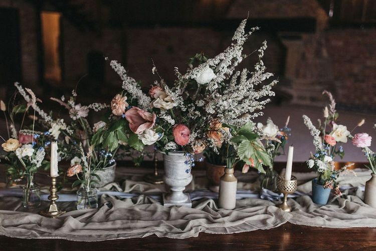 Seasonal spring wedding flower centrepieces in different size vases