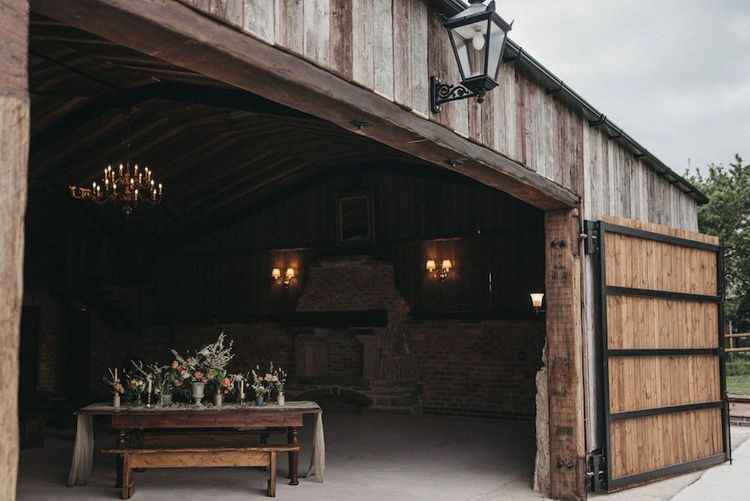 Barn doors open at Willow March Farm wedding venue  for inspiration with lace wedding jacket