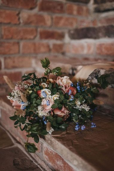 Seasonal Spring wedding bouquet with ranunculus and foliage
