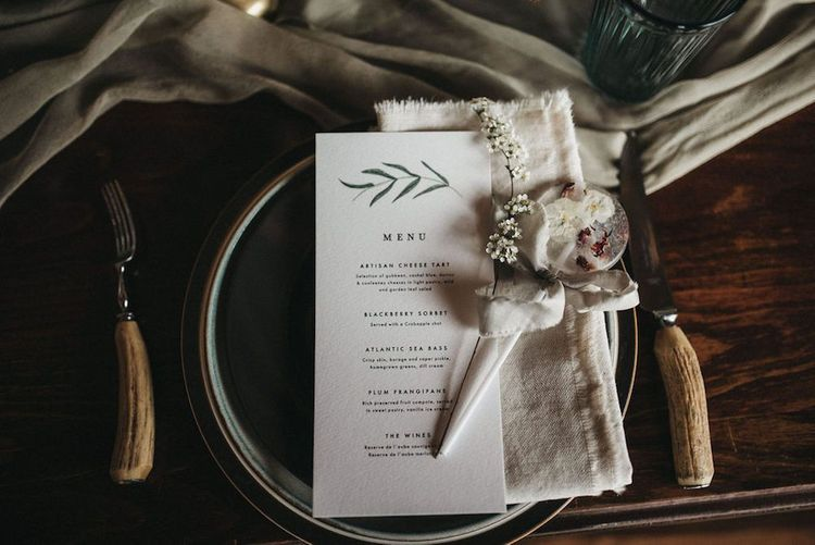 Place setting with menu card and lollipop wedding favour for inspiration with lace wedding jacket