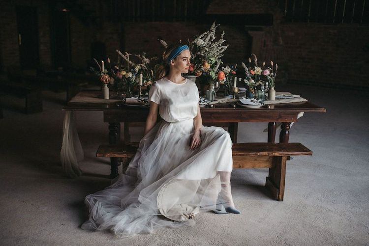Bride in Susanna Greening Designs wedding dress sitting at a rustic reception table