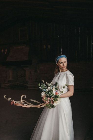 Bride in Susanna Greening Designs wedding dress holding a pastel bouquet and wearing a blue headpiece