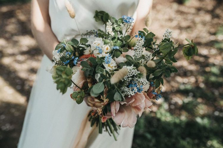 Pastel flower wedding bouquet with seasonal blooms for inspiration with lace wedding jacket
