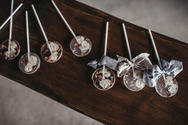 Flower pressed lollipop treats tied with silk ribbon for inspiration with lace wedding jacket