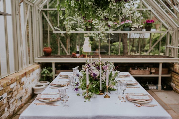 Floral Table Centrepiece with Taper Candles | Violet Flower Filled Secret English Garden Inspiration in a Glasshouse Styled by The Timeless Stylist | Maja Tsolo Photography