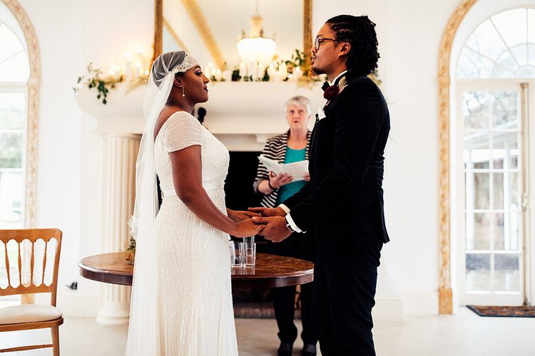 Black Bride in Juliet Cap Veil and Eliza Jane Howell Wedding Dress and Groom in Tuxedo Holding Hands During The Wedding Ceremony