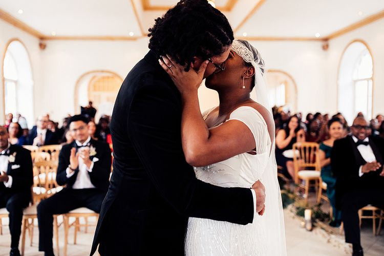 Black Bride in Juliet Cap Veil and Eliza Jane Howell Wedding Dress and Groom in Tuxedo Kissing at the Altar